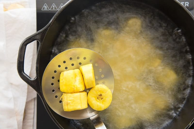The fried plantains are removed from a black pot of oil
