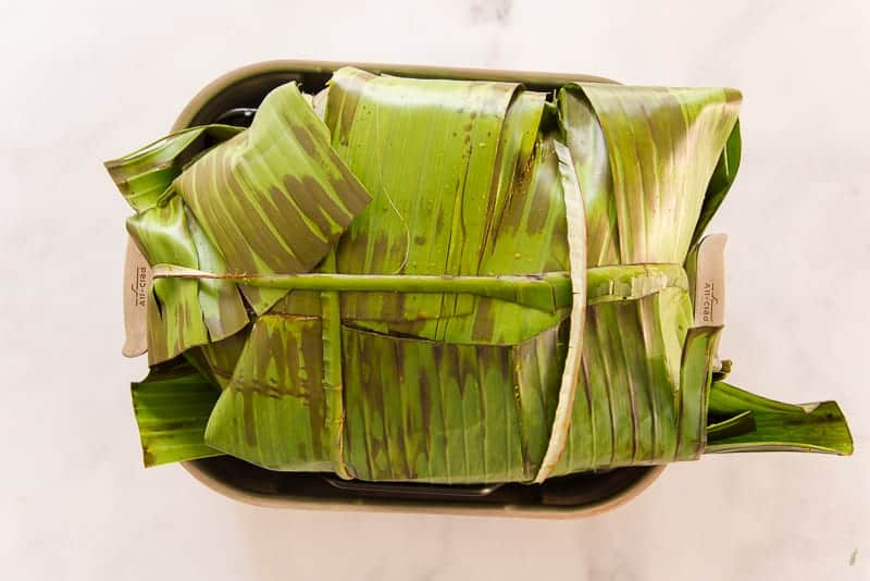 The turkey is wrapped in damp banana leaves before being covered with foil and roasted