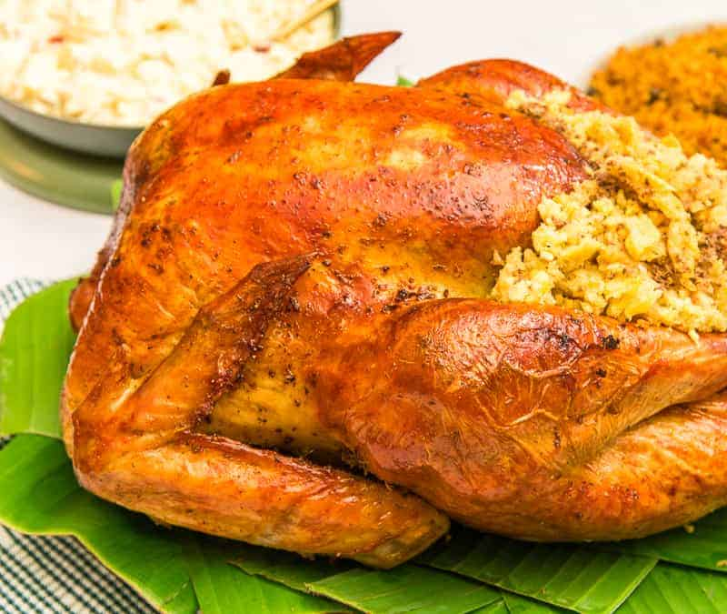 The roasted turkey is allowed to rest on a bed of banana leaves