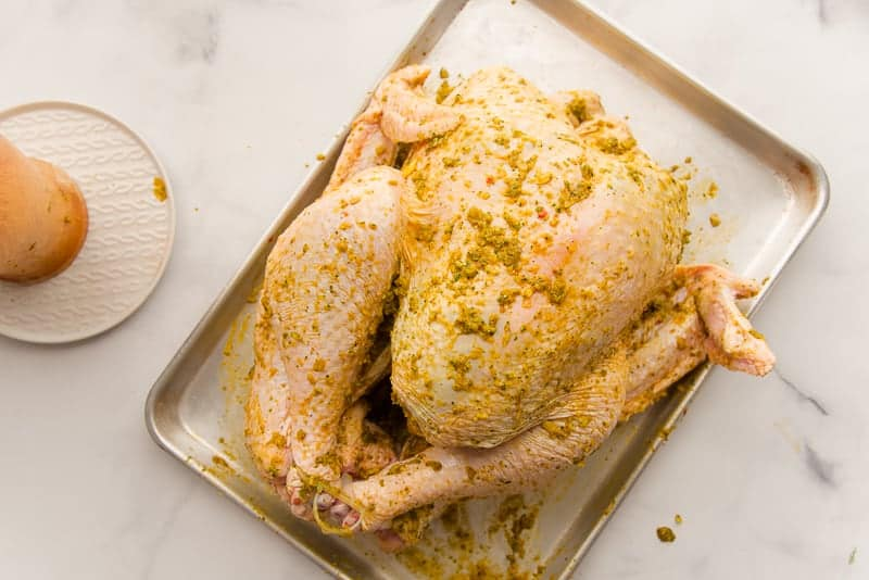 The turkey with the lechon seasoning is on a silver sheet pan