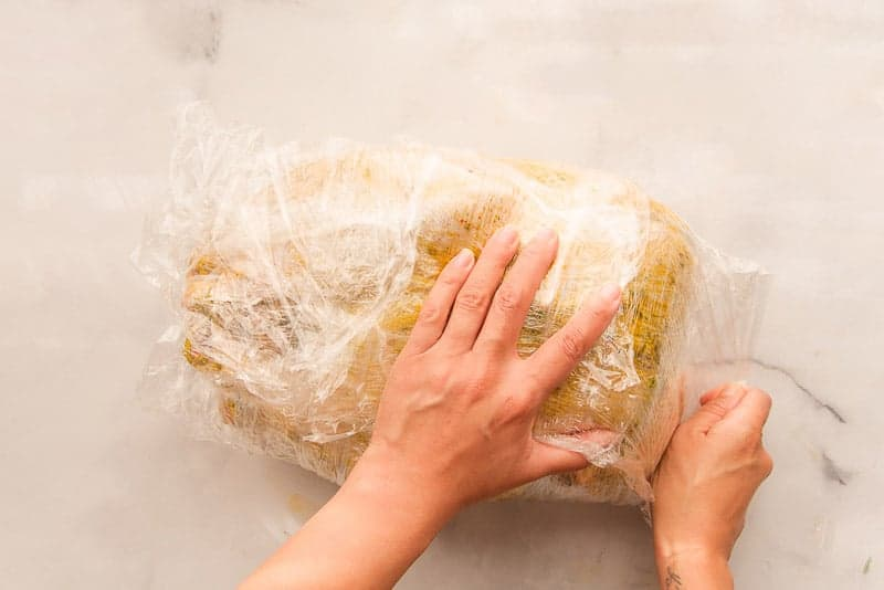 The turkey is wrapped tightly in plastic wrap before being marinated for 1-2 days