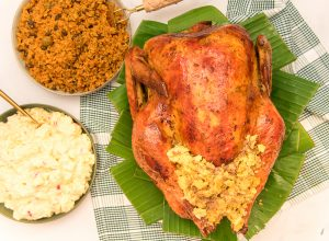The Pavochon with Mofongo Stuffing on a bed of banana leaves next to bowls of potato salad and yellow rice