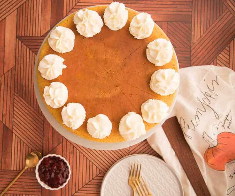 A pumpkin cheesecake decorated with whipped cream on a wooden surface