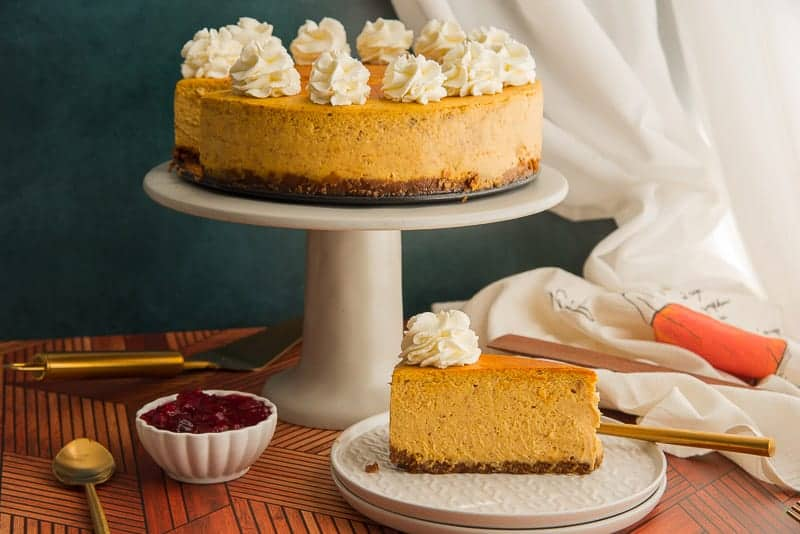 A slice of pumpkin cheesecake on a stack of white plates in front of a gray cake stand with a cheesecake on it
