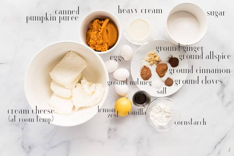 The ingredients needed to make pumpkin cheesecake: cream cheese, pumpkin puree, heavy cream, sugar, spices, eggs, lemon zest, vanilla, and cornstarch pictured on a marble surface
