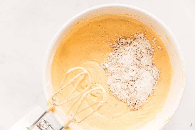 Cornstarch and spices are added to orange batter in a white mixing bowl