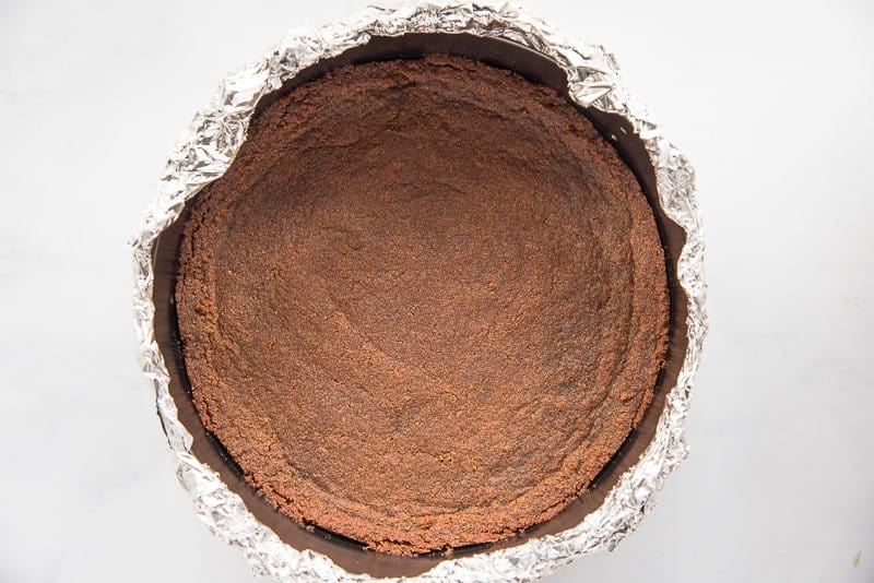 The gingersnap crust is baked in a pan that is wrapped in aluminum foil
