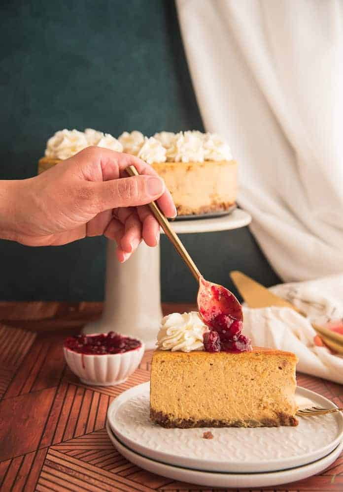 A hand spoons a dollop of cranberry sauce on to the desert on a white plate