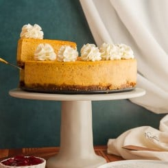 Slice of pumpkin cheesecake is being lifted from the Cheesecake on a gray cake stand