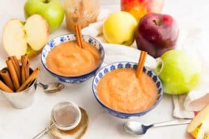 Two blue and white floral bowls of Slow Cooker Cinnamon Applesauce surrounded by apples of different colors and a sifter of cinnamon