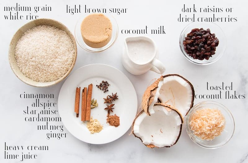 Ingredients needed to make arroz con dulce: medium grain white rice, light brown sugar, coconut milk, dark raisins or cranberries, toasted coconut flakes, cinnamon, allspice, star anise, cardamom, nutmeg, and ginger. Not pictured: heavy cream and fresh lime juice.