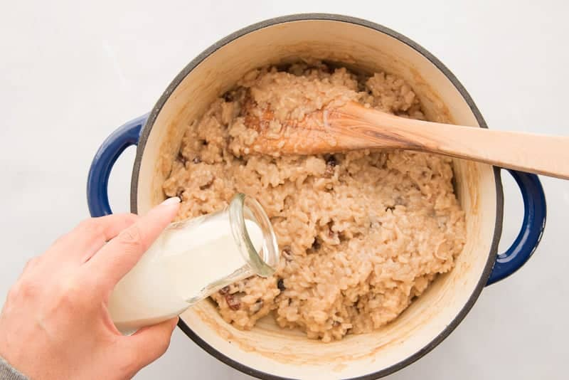 A hand pours heavy cream from a clear milk bottle into a blue pot of arroz con dulce. A wooden spoon is in the pot.