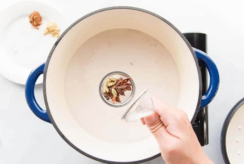 Whole spices are added to a tea strainer before being steeped in hot coconut milk in a blue pot.