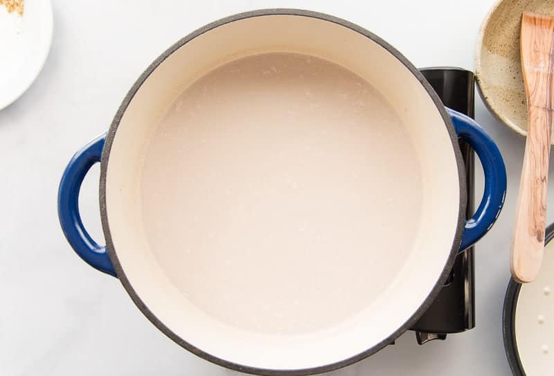 The coconut milk is brought up to a boil after the rice has been stirred into the blue pot.