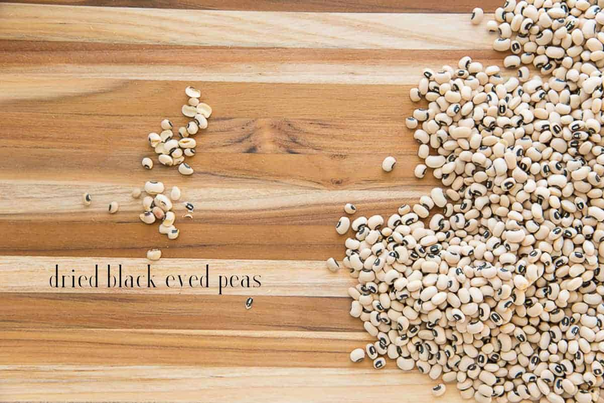 Dried peas on a wooden cutting board are sorted before being soaked