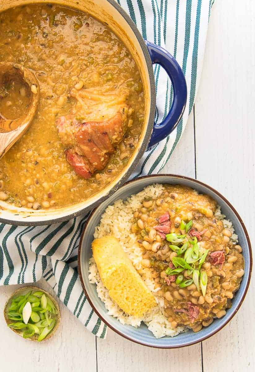 Portrait image of a blue dutch oven filled with black eyed peas and a ham hock next to a blue bowl of black eyed peas and rice