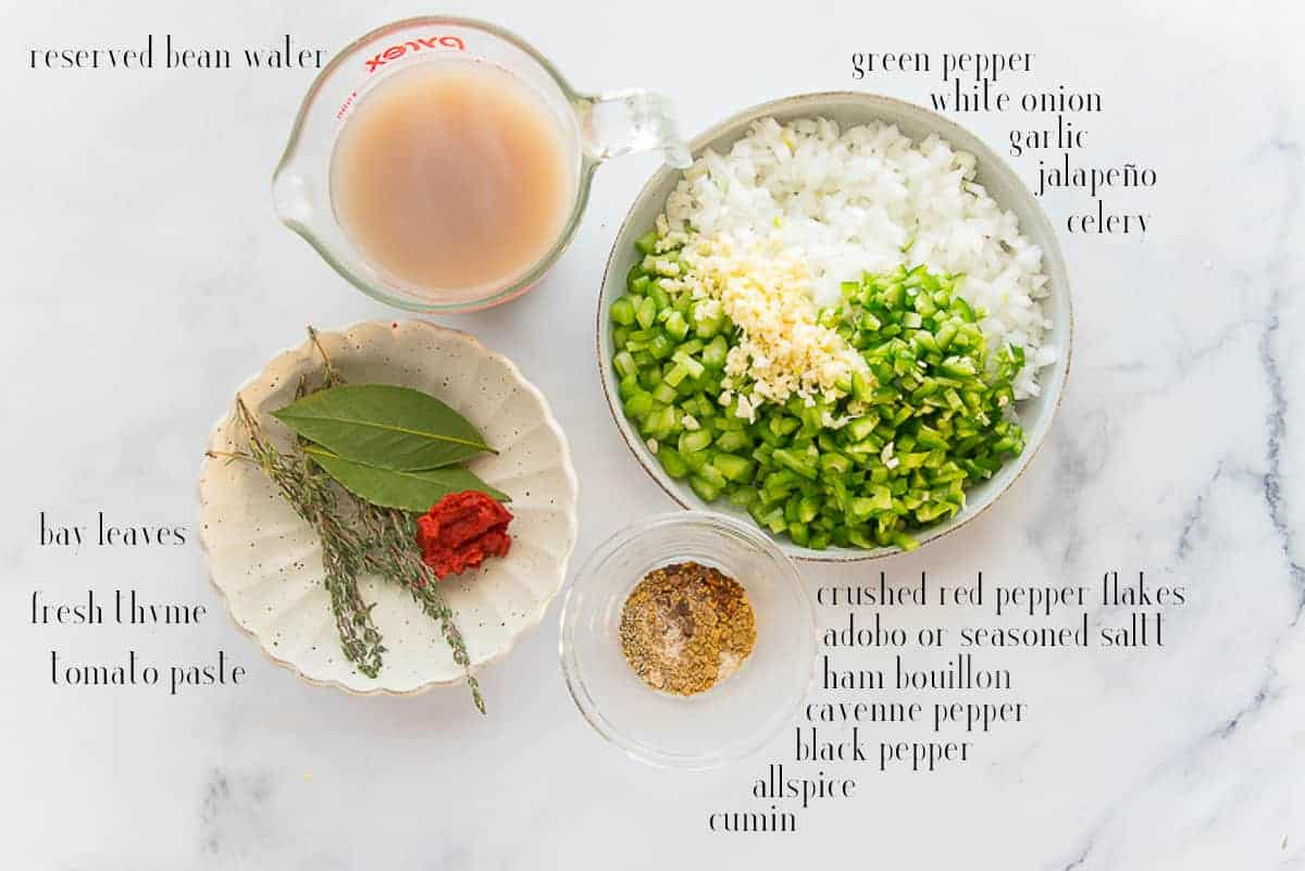 Ingredients needed shown on a white marble surface: reserved bean water, green pepper, onion, garlic, jalapeño, celery, red pepper flakes, adobo, bouillon, cayenne, black pepper, allspice, cumin, tomato paste, thyme, and bay leaves