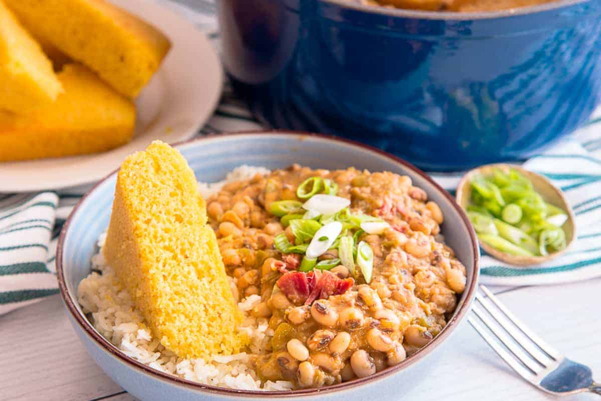 A closeup image of a blue bowl filled with white rice and topped with black eyed peas garnished with sliced green onions. A wedge of yellow cornbread sits on the left