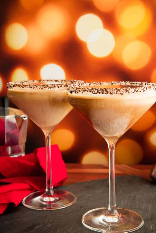 Two martini glasses of Café con Leche Martini cocktails in front of a festive background. Red napkin and coffee pot to the left