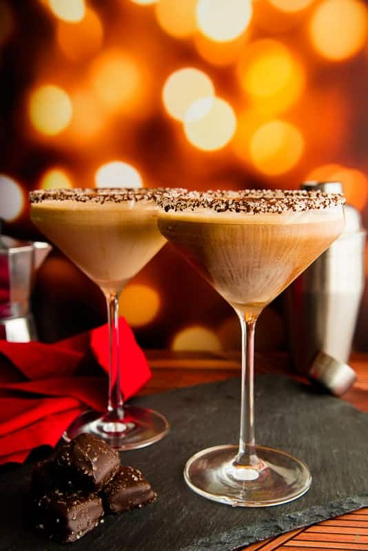 Portrait image of two martini glasses with café con leche martini mix on a black slate board next to chocolate candies a red napkin and a silver cocktail shaker