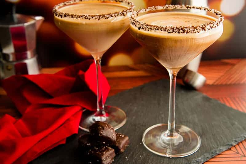 Horizontal image of two Café con Leche Martini on a black slate surface next to chocolate candies and a red napkin.