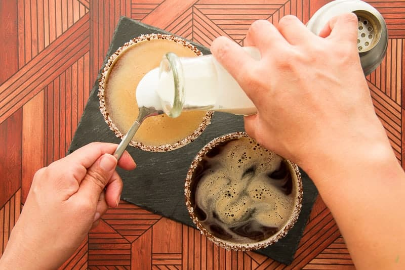 One hand pours heavy cream over a spoon held in the left hand to float it on the surface of the Café con Leche Martini