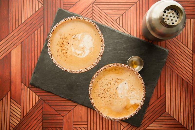 Flatlay image of two glasses of Café con Leche martini on a black surface next to a silver cocktail shaker.