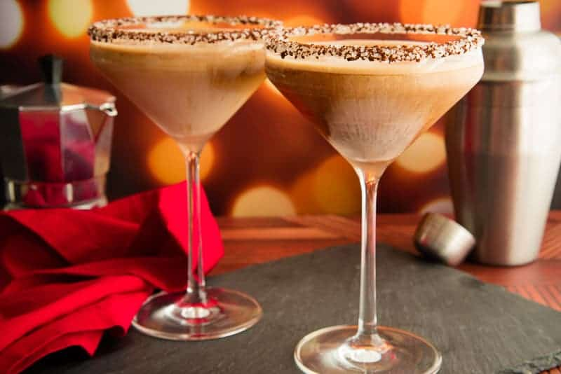 Horizontal image of two Café con Leche martinis on a black surface next to a red napkin