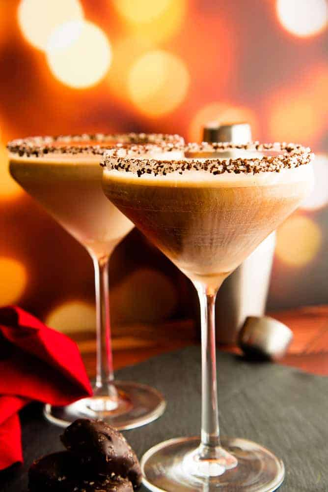 Lead image of Two martini glasses rimmed with ground espresso and sugar crystals and filled Café con Leche Martini on a black slate surface next to a pile of chocolate candies.