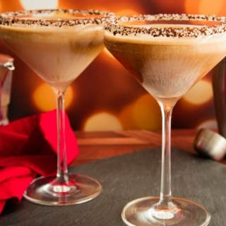 Preview image of Two martini glasses rimmed with ground espresso and sugar crystals and filled Café con Leche Martini on a black slate surface next to a pile of chocolate candies.