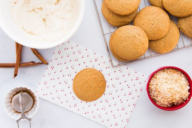 Baked coquito cookies on a silver rack. One coquito cookie is on a white piece of paper with floral print. Left of image: red bowl filled with toasted coconut.Top left of image: white coquito buttercream in a white ceramic bowl.
