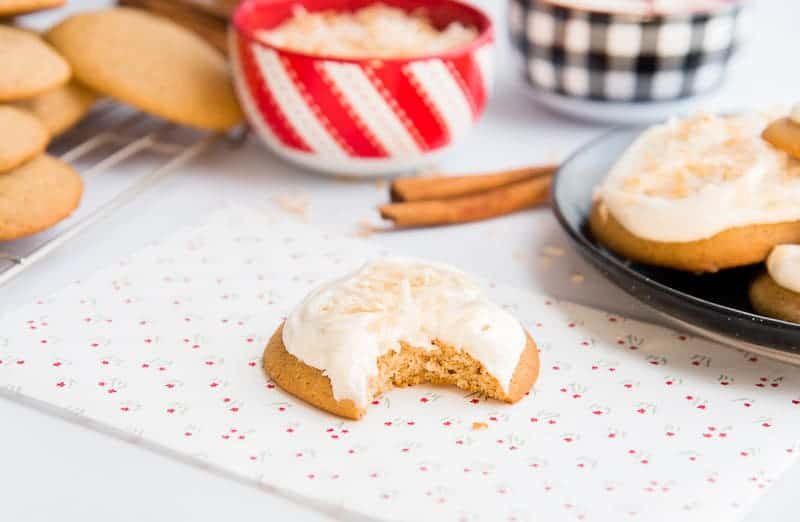 Horizontal image of a coquito cookie with a bite taken out of it on a red and green floral paper. Center background candy cane-striped bowl filled with toasted coconut.