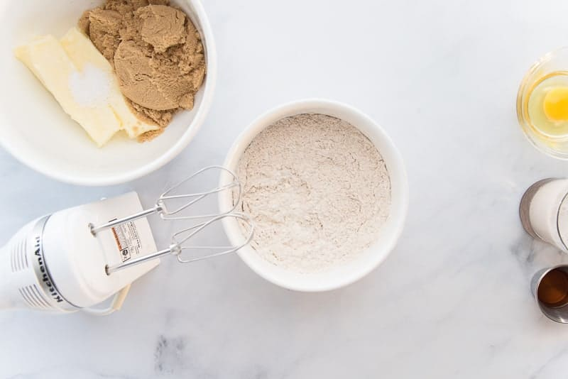 The dry ingredients are blended together with the beaters of an electric hand mixer and a white ceramic bowl.