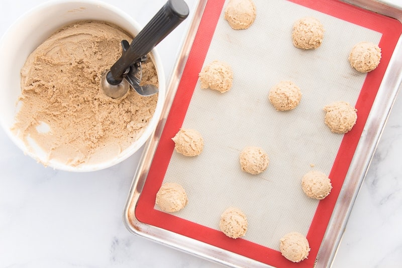 The chilled coquito dough in a white ceramic mixing bowl. A portion scoop protrudes from the dough. A silver sheet pan with scoops of coquito dough is ready to be placed in the oven.