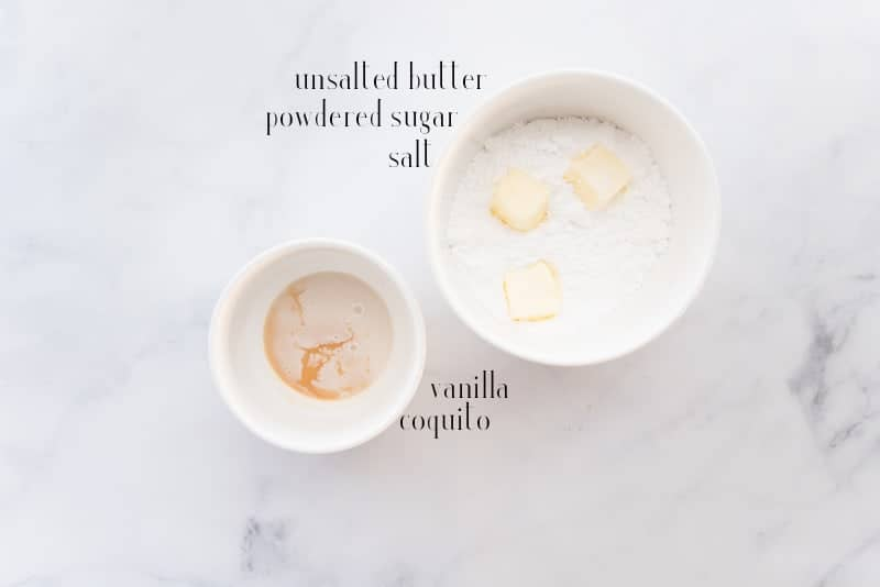 The ingredients needed to make coquito buttercream: vanilla, coquito, powdered sugar, unsalted butter, and salt in white ceramic bowls.