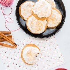 Lead image of coquito cookies. Coquito cookies on a black plate garnished with toasted coconut, a cookie with a bite removed on a white piece of paper with floral print. Bottom right of image: a red bowl filled with toasted coconut. Top-left image: red and white striped spool of string.