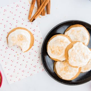 A black plate is piled with a stack of coquito cookies topped with coquito buttercream and toasted coconut flakes. To the left on a white and floral print piece of paper is a coquito cookie with a bite taken out of it.