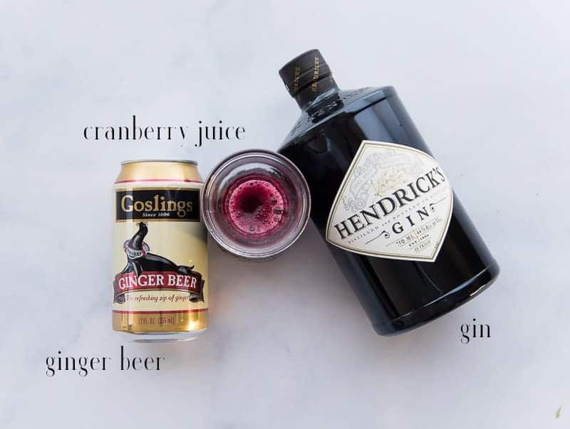 The ingredients needed to make a ginger rickey: ginger beer, cranberry juice, and gin