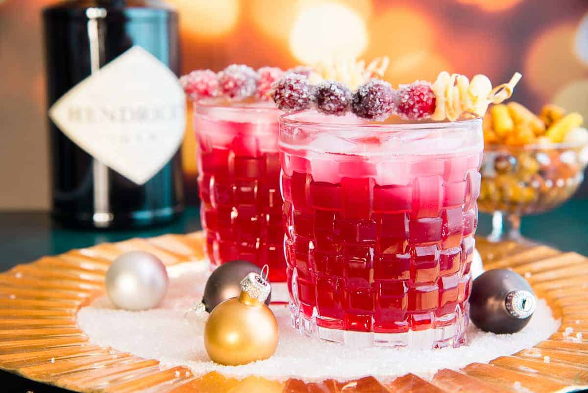 Horizontal image of two old fashioned glasses filled with ginger Rickey cocktail garnished with sugared cranberries and furled ginger.