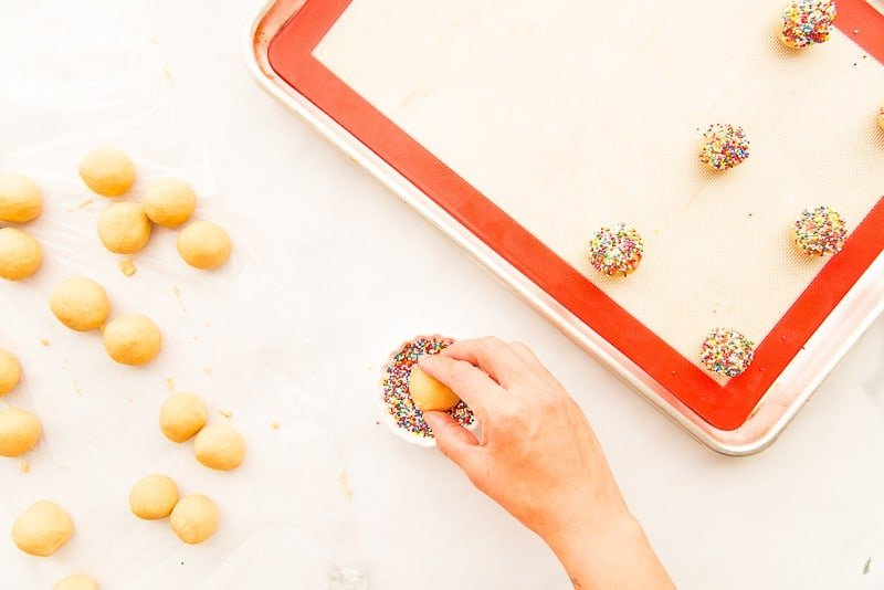 A hand dips a rolled ball of cookie dough into rainbow colored sprinkles.