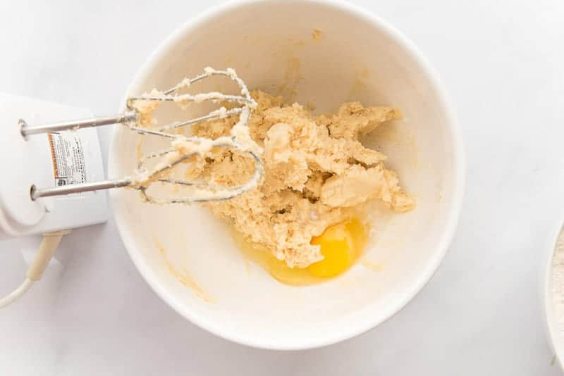 An egg and almond extract are added to the butter and sugar mixture in a white ceramic bowl.