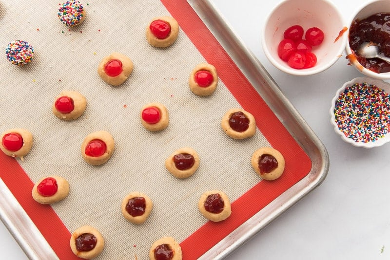 The filled cookies on a red and white silicone mat prior to being baked