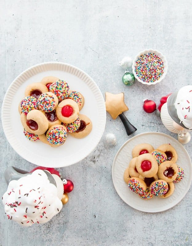 A portrait image of a white cake plate with mantecaditos back on top a white ceramic plate with more cookies that bottom right a white dish of sprinkles the top right.
