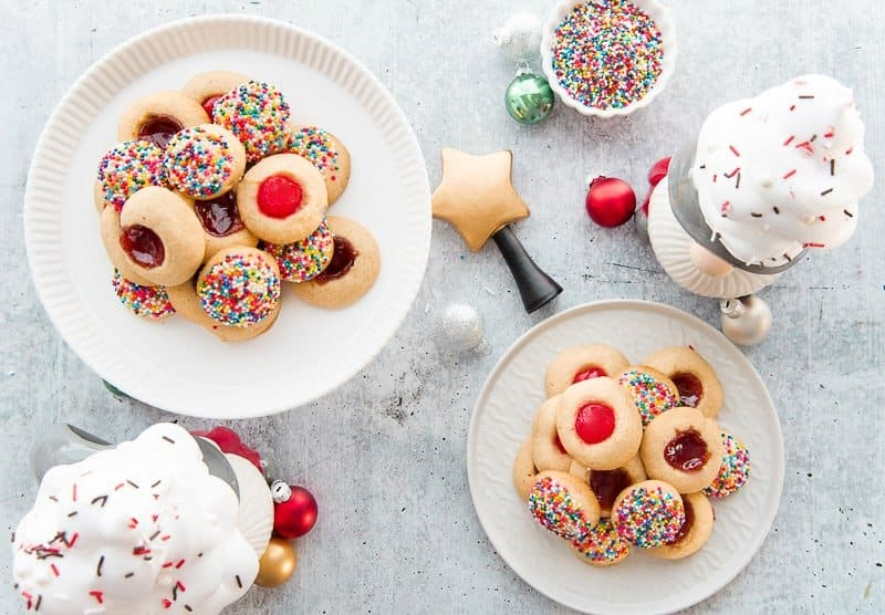 Horizontal image of mantecaditos on a white ceramic plate. A gnome mug with whipped cream and a cherry on top on right background.