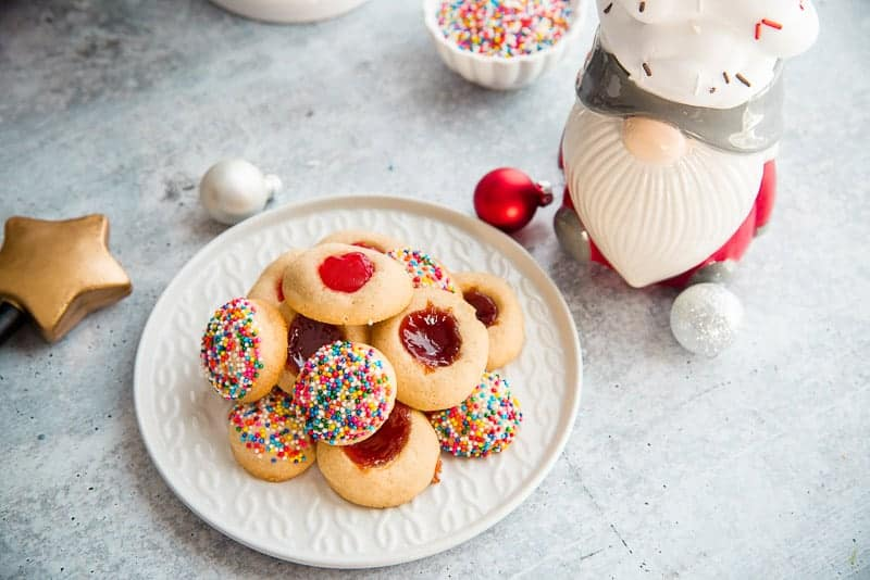 A white ceramic plate with cookies gnome mug topped with whipped cream metallic ornaments scattered about on a gray surface
