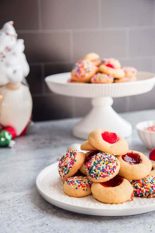 Horizontal image of a white cake stand topped with mantecaditos bottom right of image is a white ceramic plate topped with more cookies bottom right white bowl filled with rainbow sprinkles.