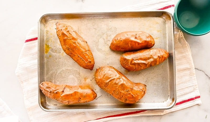 The roasted sweet potatoes on a silver sheet pan Which lays on a white towel with red stripes