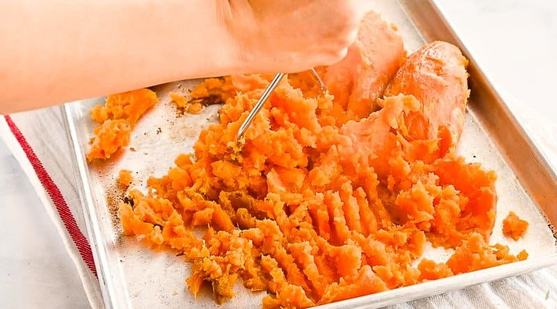Hand uses a potato masher and mashed roasted sweet potatoes on a silver sheetpan