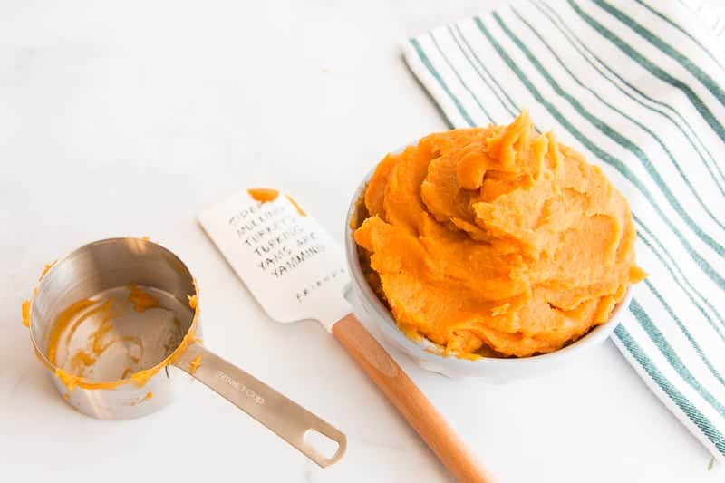 Horizontal image: bowl of sweet potato puree, white and wooden rubber spatula, silver measuring cup, and striped kitchen tile