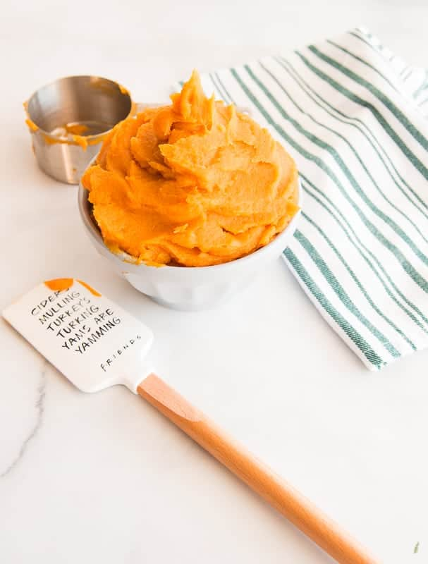 Portrait image: gray bowl filled with sweet potato puree green and white kitchen towel white and wooden rubber spatula silver measuring cup